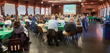 Image of a group of 100 people listening to a lecture at Oregon Ridge Lodge